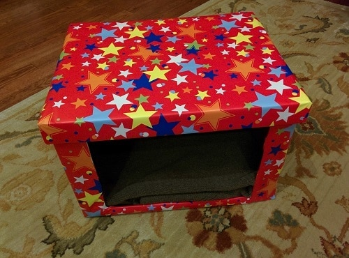DIY Cardboard cat bed covered in red fabric with different colored stars.